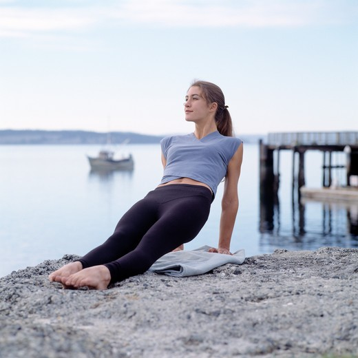 Stock Photo: 1626R-15320 Caucasian Woman Doing Yoga On A Rock Overlooking A Lake