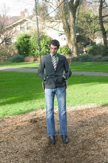 Stock Photo: 1626R-15833 Fashionable Male Twenty Something Playing On A Swing Set