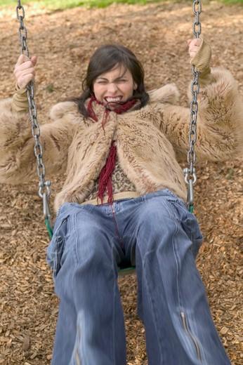 Stock Photo: 1626R-15836 Stylish Urban Female Twenty Something Swinging Playfully In The Park