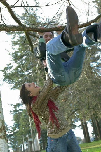 Twenty Something Female Helping Her Boyfriend Do A Pull Up In The Park : Stock Photo