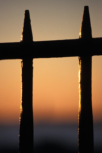 Looking Through An Iron Fence At Sunset : Stock Photo