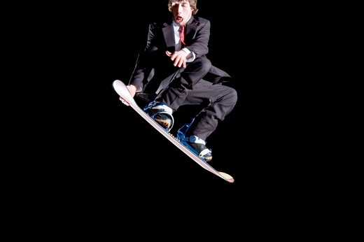 Stock Photo: 1626R-19944 Young Man Snowboarding in a Suit and Tie