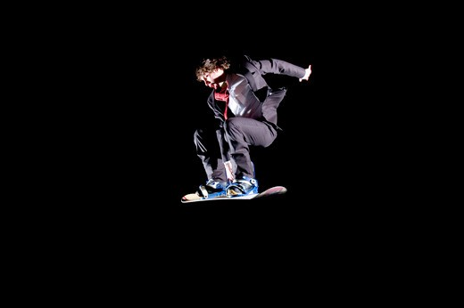 Young Man Snowboarding in a Suit and Tie : Stock Photo