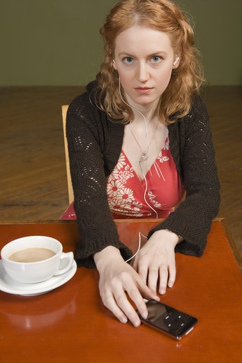 Stock Photo: 1626R-20428 Young Woman with Headphones and Coffee
