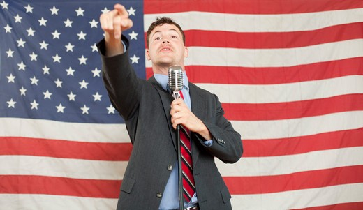 Stock Photo: 1626R-22945 Young politician pointing and holding microphone stand
