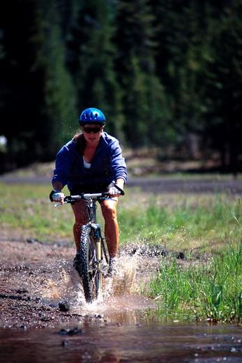 Stock Photo: 1626R-5104 Woman Mountain Biking Into Stream
