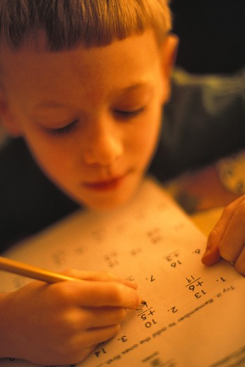 Boy (8-9) calculating on paper : Stock Photo