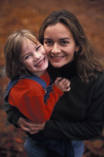 Stock Photo: 1626R-8181 Mother holding daughter (3-4), smiling, portrait