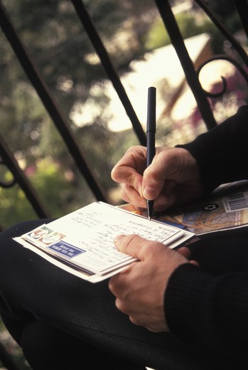Person writing on postcard, close-up : Stock Photo