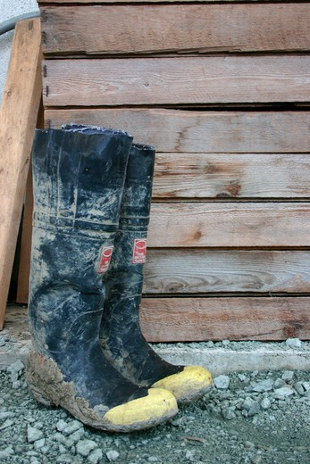 Galoshes by wooden structure, close-up : Stock Photo