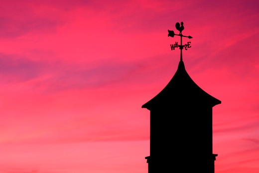 Weather vane on tower at dusk : Stock Photo