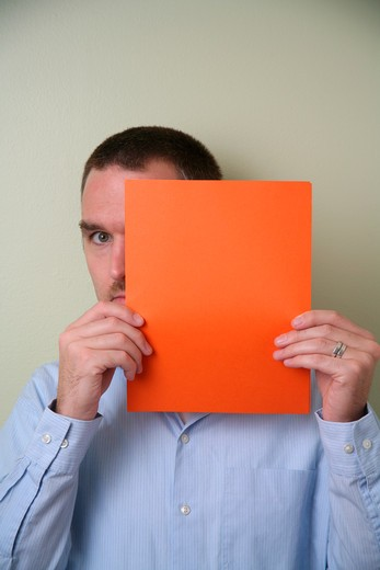 Stock Photo: 1626R-9634 Young man holding blank card, portrait