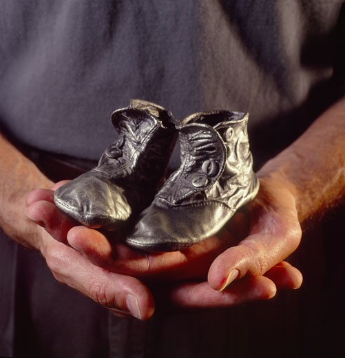 Stock Photo: 1627R-144 Mid section view of a man holding a pair of baby booties