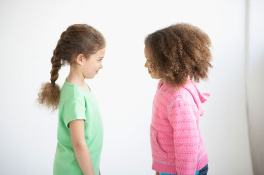 Stock Photo: 1628-0225 Side profile of two girls standing face to face