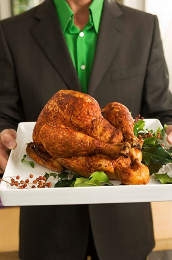 Stock Photo: 1630R-211 Mid section view of a man holding a roasted turkey on a tray