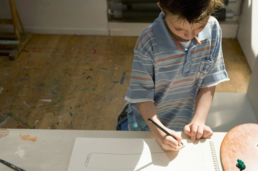 High angle view of a boy drawing on a sketch pad : Stock Photo