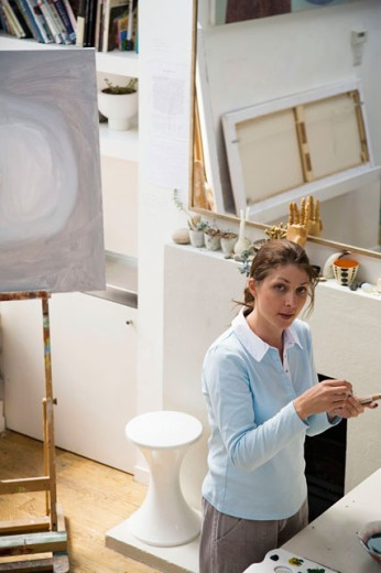 High angle view of a young woman holding a paintbrush : Stock Photo