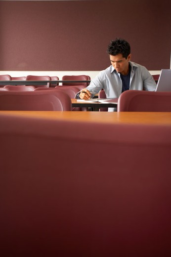 College student sitting in a lecture hall and studying : Stock Photo