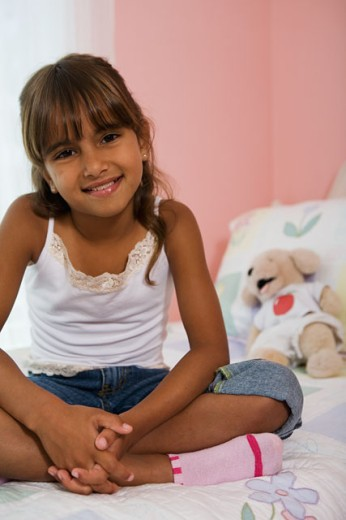 Stock Photo: 1646R-204 Portrait of a girl sitting in the bed and smiling