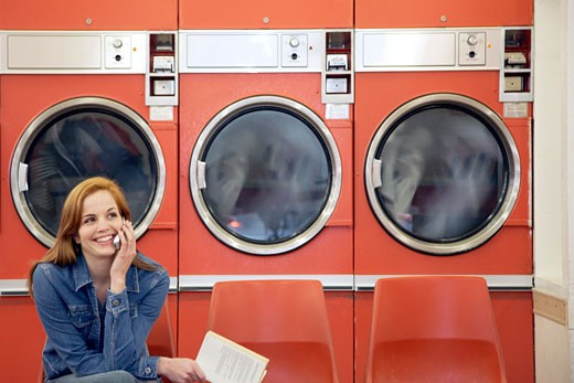 Woman Talking on Cell Phone in Laundromat : Stock Photo