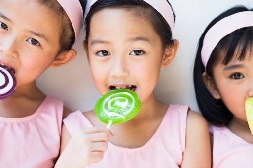 Girls Licking Lollipops : Stock Photo