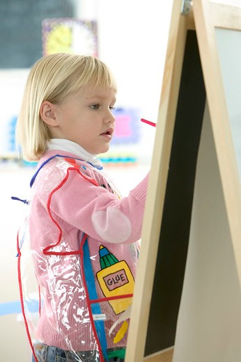 Girl Painting on Easel : Stock Photo