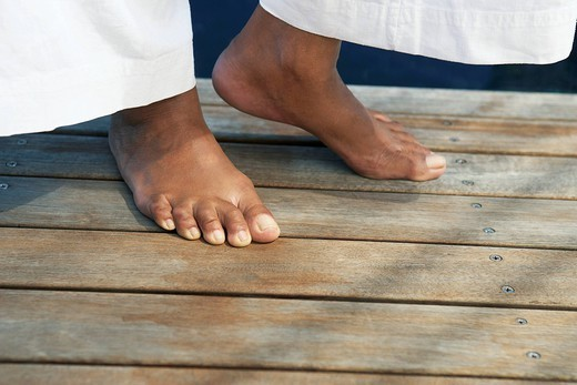 Feet of woman on wooden deck : Stock Photo