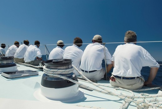 Stock Photo: 1654-1020 Sailing crew sitting on side of yacht on ocean back view