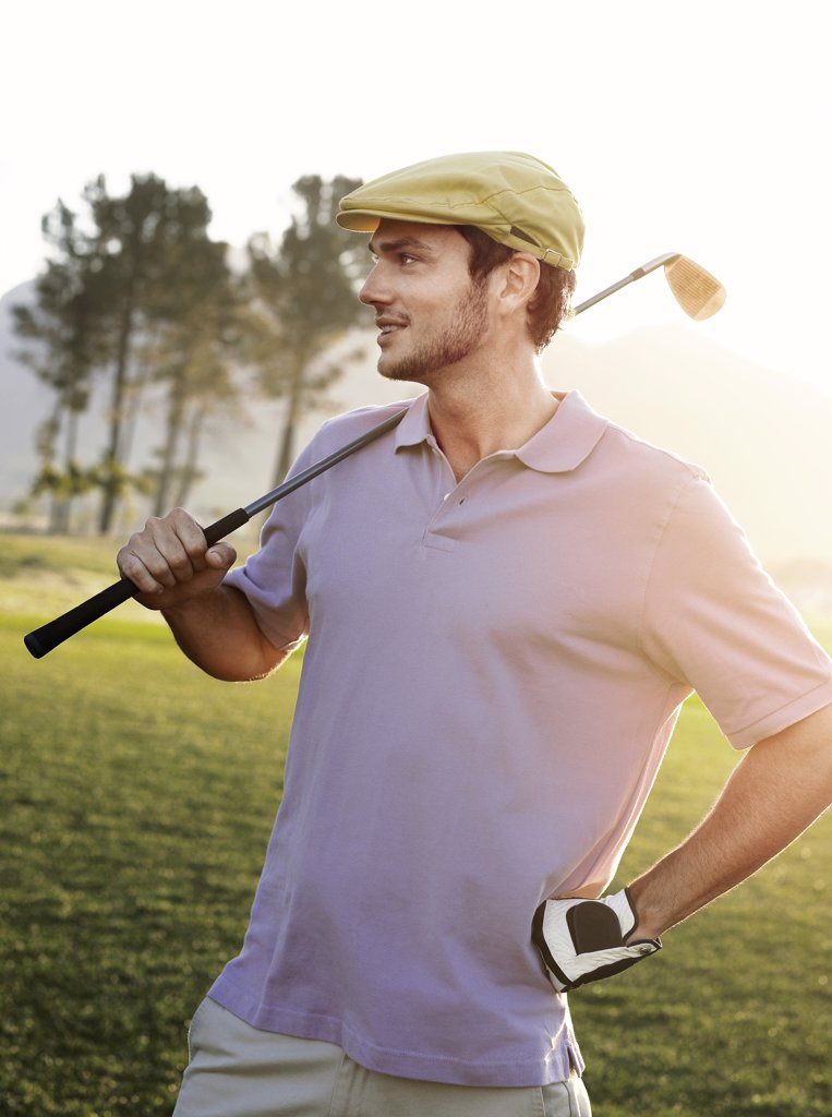 Stock Photo: 1654-12452 Young male golfer standing on course holding club on shoulder