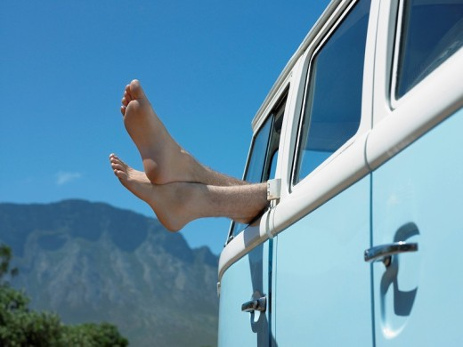 Person in parked camper van feet sticking out of window close up : Stock Photo