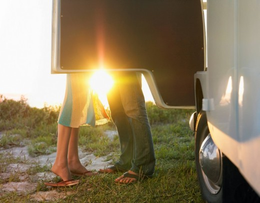 Young couple face to face beside camper van low section : Stock Photo