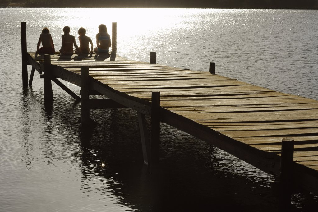 Four children 7_9 sitting on dock by lake back view. : Stock Photo