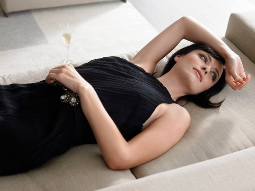 Woman lying on couch holding champagne glass in living room : Stock Photo