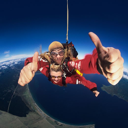 Two skydivers giving thumbs_up in mid_air portrait : Stock Photo