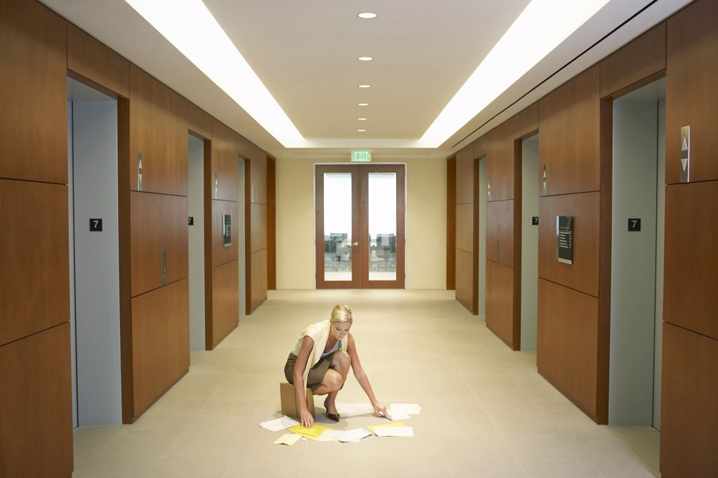 Woman in Office Corridor Sorting Documents : Stock Photo