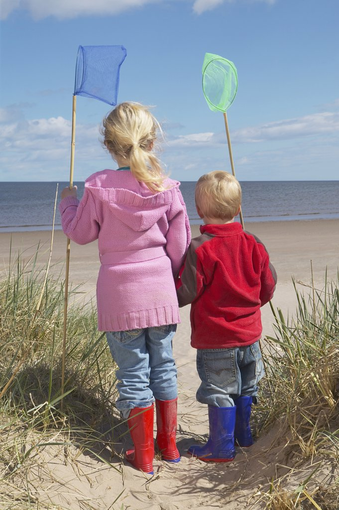 Brother and Sister Holding Dip Nets by the Ocean : Stock Photo