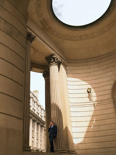 Businessman using mobile phone in neo_classical style building : Stock Photo