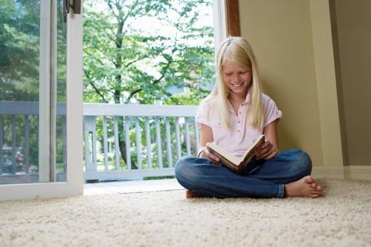 Girl 7_9 sitting cross_legged reading book smiling : Stock Photo