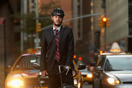 Man standing by bicycle in street portrait : Stock Photo