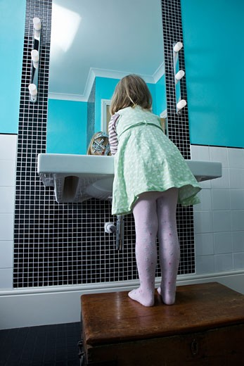 Girl 3_4 standing on wooden chest to reach bathroom sink : Stock Photo