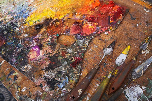 Artist´s Palette and Palette Knives Covered in Paint : Stock Photo