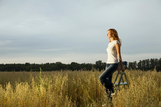 Young Woman in a Field Standing on a Step Ladder : Stock Photo