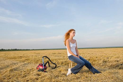 Young Woman in a Field with a Vacuum Cleaner : Stock Photo