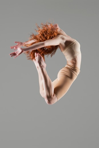 Dancer jumps with arms and legs bending nackwards : Stock Photo