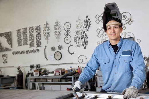 Palm Desert, California, USA. Portrait of a young male worker wearing protective gear in metal workshop : Stock Photo