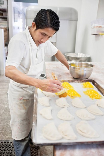 Los Angeles, California, USA. Young male baker working on preparation of pastry in bakery kitchen : Stock Photo