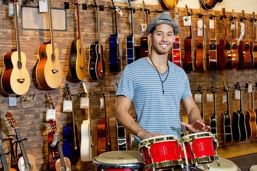 Palm Desert, California, USA. Portrait of a happy man playing bongo drums in music store : Stock Photo