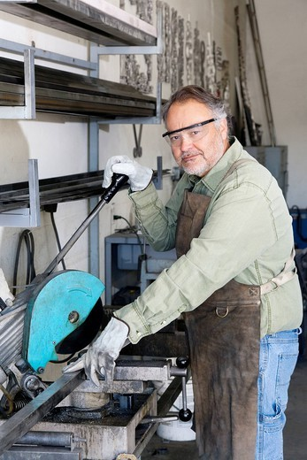 Stock Photo: 1654-49382 Palm Desert, California, USA. Portrait of a mature metalworker working with electric saw in workshop