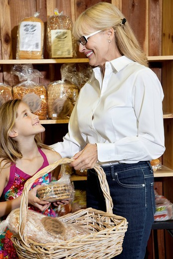 Palm Desert, California, USA. Happy senior woman with granddaughter looking at each other while holding bread basket in market : Stock Photo