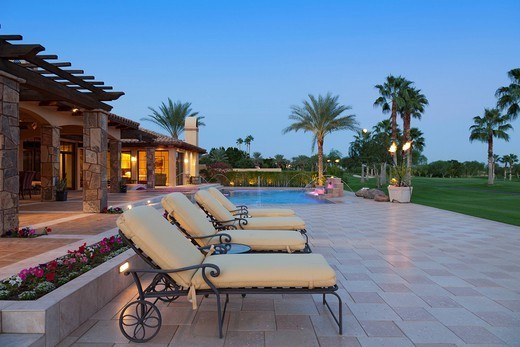Palm Springs, USA. Sun loungers in patio at poolside outside luxurious manor house : Stock Photo